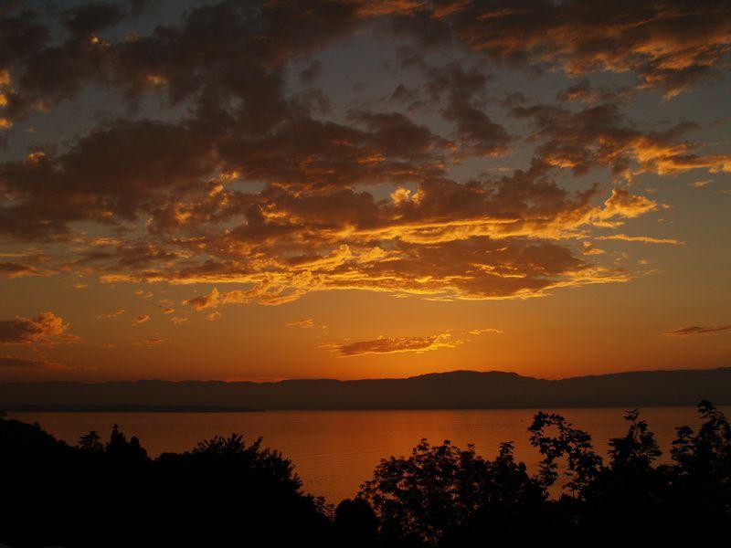 Le crépuscule et le coucher de soleil est particulièrement beau et intense sur le Lac léman, vu de France. Moment où le soleil passe derrière l'horizon, le soleil rouge, l'atmosphère, le crépuscule, la nuit, la couleur du ciel...