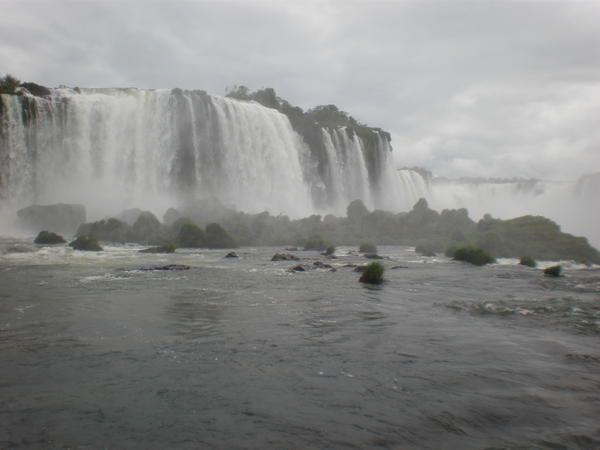 """Derrière la végétation luxuriante, les chutes d'Iguaçu vues du côté brésilien : de cascades en cascades, jusqu'à l'impressionnante """"Garganta do Diabo"""" (""""Gorge du Diable"""") et ses rideaux d'eau qui grondent et tourbillonnent : porte cachée de"""