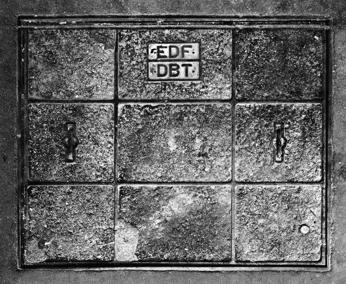 séries de plaques de sol recouvrant des connexions électriques dans les rues de Paris