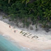 Three men rescued off deserted island after spelling 'help' with palm leaves