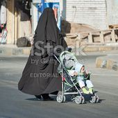 Arabic mother in burqa conducts carriage with child