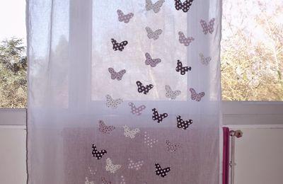 Une envolée de papillons sur un rideau