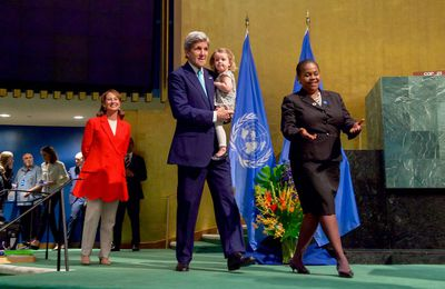 French Minister of Ecology, Sustainable Development and Energy Ségolène Royal looks on as U.S. Secretary of State John Kerry, with his granddaughter, walks accross the stage to signing the COP21 Climate Change Agreement