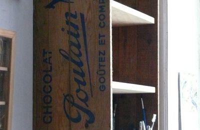 Étagère murale dans une caisse ancienne de chocolat Poulain