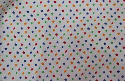 Coton imprimé petites étoiles multicolores sur fond blanc