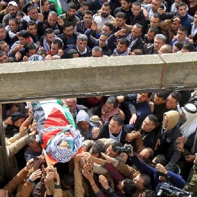 Mourners carry the body of Palestinian gunman