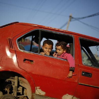 Palestinian children play in damaged cars in Gaza