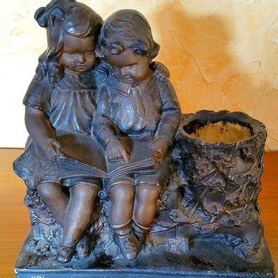 Ancien groupe en plâtre représentant un couple d'enfants assis lisant.